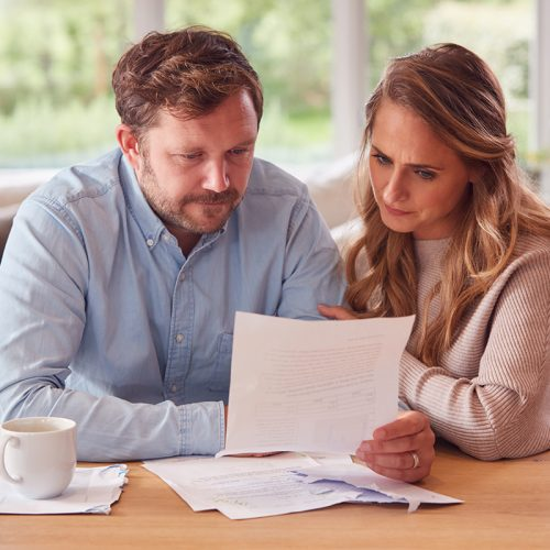 Worried Couple With Bills And Digital Tablet Sitting At Table At Home Reviewing Domestic Finances